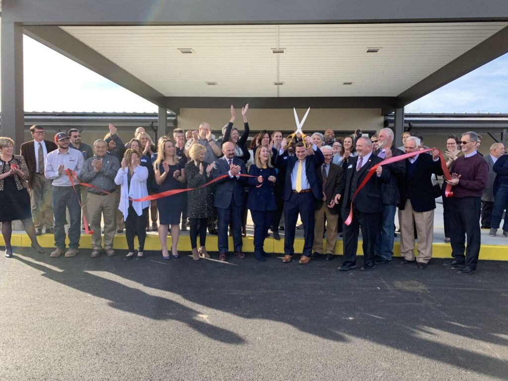 Dr. H cuts ribbon surrounded by friends of MRC